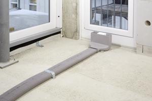 """<div class=""""bildtext_1"""">Verlegung der Luftverteilung auf dem Rohboden</div> <div class=""""bildtext_1"""">1. Die Flachovalrohre und das Luftdurchlassgehäuse werden montiert. Ein System mit Fixierschieber und Dichtring verhindert das versehentliche Ausziehen der Rohre und stellt die luftdichte Verbindung sicher. Geschlossene Luftdurchlässe schützen in dieser Phase vor Verschmutzung.</div>"""