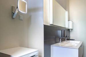 """<div class=""""bildtext_1""""></div> <div class=""""bildtext_1"""">Der Waschtisch und Spiegel, die Armaturen, Möbel und der Kosmetikspiegel von Keuco geben dem WC eine exklusive Note und besonderen Komfort. </div>"""