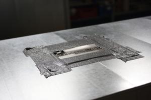 """<div class=""""bildtext_1"""">Der Kanal enthält künstlich eingebaute Leckagestellen und Bohrlöcher unterschiedlicher Größen, die im Versuch nach und nach vom Dichtstoff verschlossen werden. Gestanztes Aeroseal-Lochblech setzt sich nach und nach mit Dichtstoff zu.</div>"""
