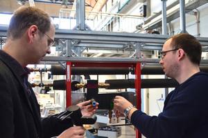 """<div class=""""bildtext_1"""">Prof. Dr. Carsten Bäcker (l.) und Stefan Brodale schließen eine Armatur an ihr aufgebautes Trinkwasser-Installationsmodell mit Warm- und Kaltwasserleitung an. </div>"""