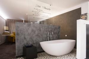 """<div class=""""bildtext_1"""">Eine halbhohe Vorwand trennt die freistehende Badewanne vom Schlafbereich. Poesie begleitet den Gast bei der Entspannung vom Alltag. </div>"""