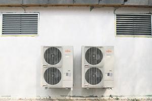 """<div class=""""bildtext_1"""">Die beiden Fujitsu-Außeneinheiten für die Klimatisierung der Trainingshalle, darüber Zu- und Abluftgitter des RLT-Geräts.</div>"""