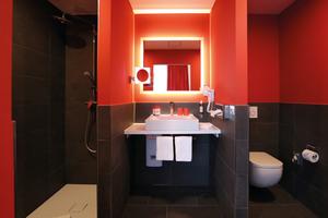 """<div class=""""bildtext_1"""">In den Badezimmern treffen rote Wände und schwarze Fliesen auf die eleganten Waschtische und Duschflächen der Kaldewei """"Cono"""" Serie aus Stahl-Email in Alpinweiß.</div>"""