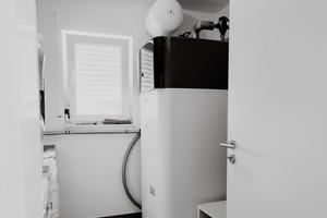 """<div class=""""bildtext_1"""">Die Inneneinheit mit integriertem 500 Liter Wärmespeicher benötigt nur 0,62 m² Fläche und steht bei Familie Müller zusammen mit Waschmaschine, Trockner und Gefriertruhe im Hauswirtschaftsraum.</div>"""