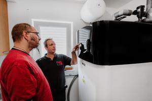 """<div class=""""bildtext_1"""">Installateur Oliver Fleig (rechts), Geschäftsführer von Fleig Wärmetechnik aus Billigheim bei Heilbronn, weist den Hausherrn in die Bedienung der """"Altherma 3 R ECH2O"""" ein.</div>"""