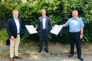 Ulrich Stahl (Vorstandsvorsitzender) und Axel Grimm (Geschäftsführer) überreichen Michael Muerköster die Urkunden über langjährige Mitgliedschaft der Unternehmen Danfoss GmbH und Danfoss/DEVI.