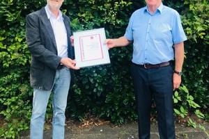 Ulrich Stahl (Vorstandsvorsitzender) überreicht Stefan Peetz von der ATHE-Therm Heizungstechnik GmbH die Urkunde über langjährige Mitgliedschaft.