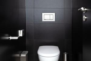 """<div class=""""bildtext_1"""">Klassisch-schlicht: Die gerundete Form des weißen Geberit """"Renova""""-Wand-WCs sowie die mattchrom-lackierte Oberfläche der Betätigungsplatte """"Sigma30"""" kommen vor der schwarz gefliesten Wand besonders gut zur Geltung.</div>"""