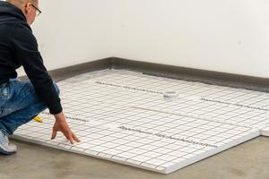 """<div class=""""bildtext_1"""">Das Fußbodenheizungssystem besteht aus einer 30mm Trittschallplatte mit einer oben sowie unten angebrachten Gewebefolie, um Risse in der Styroporplatte beim Einschneiden mit dem Nutenschneider zu vermeiden.</div>"""
