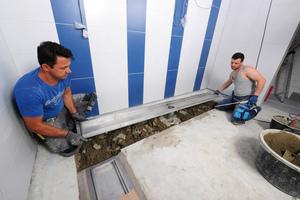 """<div class=""""bildtext_1"""">Im neuen Duschbereich verbauten die Verarbeiter Industrie- und Küchenrinnen der Firma Richard Brink. Hier werden die maßgefertigten Produkte aus Edelstahl in die dafür ausgesparten Bodenbereiche eingelegt. Zement und zusätzlicher Flexkleber bilden den Untergrund.</div>"""