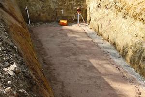 """<div class=""""bildtext_1"""">Nordseite der Schlossberghalle: Baugrube, nach Entnahme des alten Öltanks, für den Pelletspeicher vorbereitet mit 10-20 cm Sandauflage.</div>"""