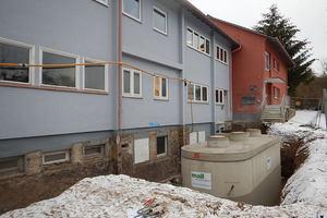 """<div class=""""bildtext_1"""">Schlossberghalle Niedereschach: Einbau des neuen Pelletspeichers unter beengten Verhältnissen auf der Nordseite. Der Fertigteil-Ovalbehälter wurde per Autokran direkt vom Lieferfahrzeug an die Stelle des früheren Öltanks gesetzt.</div>"""