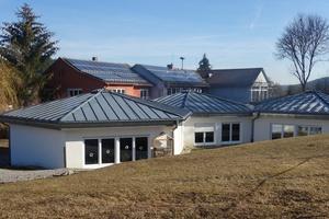 """<div class=""""bildtext_1"""">Schlossberghalle Niedereschach: Südseite mit Kindergarten und Grundschule im Vordergrund. Eine Heizzentrale versorgt alle Gebäudeteile, einschließlich Schulsporthalle und Feuerwehrgerätehaus, umgestellt 2019 von Öl auf Holzpellets.</div>"""
