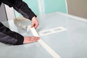 """<div class=""""bildtext_1"""">Die Verklebung der Platten erfolgt entweder durch das Montage-Kit oder den Flächenkleber. Das Spiegelklebeband ist Bestandteil des Montage-Kits. Nachdem das Klebeband und die Silikonraupen aufgetragen wurden, kann die Platte einfach an die Wand geklebt werden.</div>"""