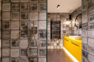 """<div class=""""bildtext_1"""">In der Suite My Way wird der """"Axor Citterio"""" mit Pingriff zum markanten, geradlinigen Gegenspieler der poppigen, gelb-grauen Badgestaltung mit einem Boden in Strukturblech-Ästhetik.</div>"""