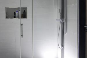 """<div class=""""bildtext_2"""">Die LED-Duschrinne taucht das Badezimmer in ein harmonisches Licht. Hierbei kommt die Ganzglasschiebetür besonders zur Geltung.</div>"""