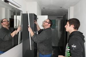 """<div class=""""bildtext_1"""">Waschtisch, Spiegelschrank und Hochschrank sind installiert. Zum Schluss werden die Möbel noch einmal ausgerichtet.</div>"""