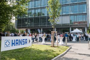 Zahlreiche Mitarbeiter und ihre Familien haben sich vor dem neuen Firmengebäude zu einem Tag der offenen Tür zusammengefunden.<br />