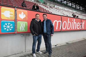 (Quelle: mobiheat GmbH) Stolz präsentieren die beiden Firmengründer Helmut Schäffer (links) und Andreas Lutzenberger die Bandenwerbung in der WWK Arena in Augsburg.